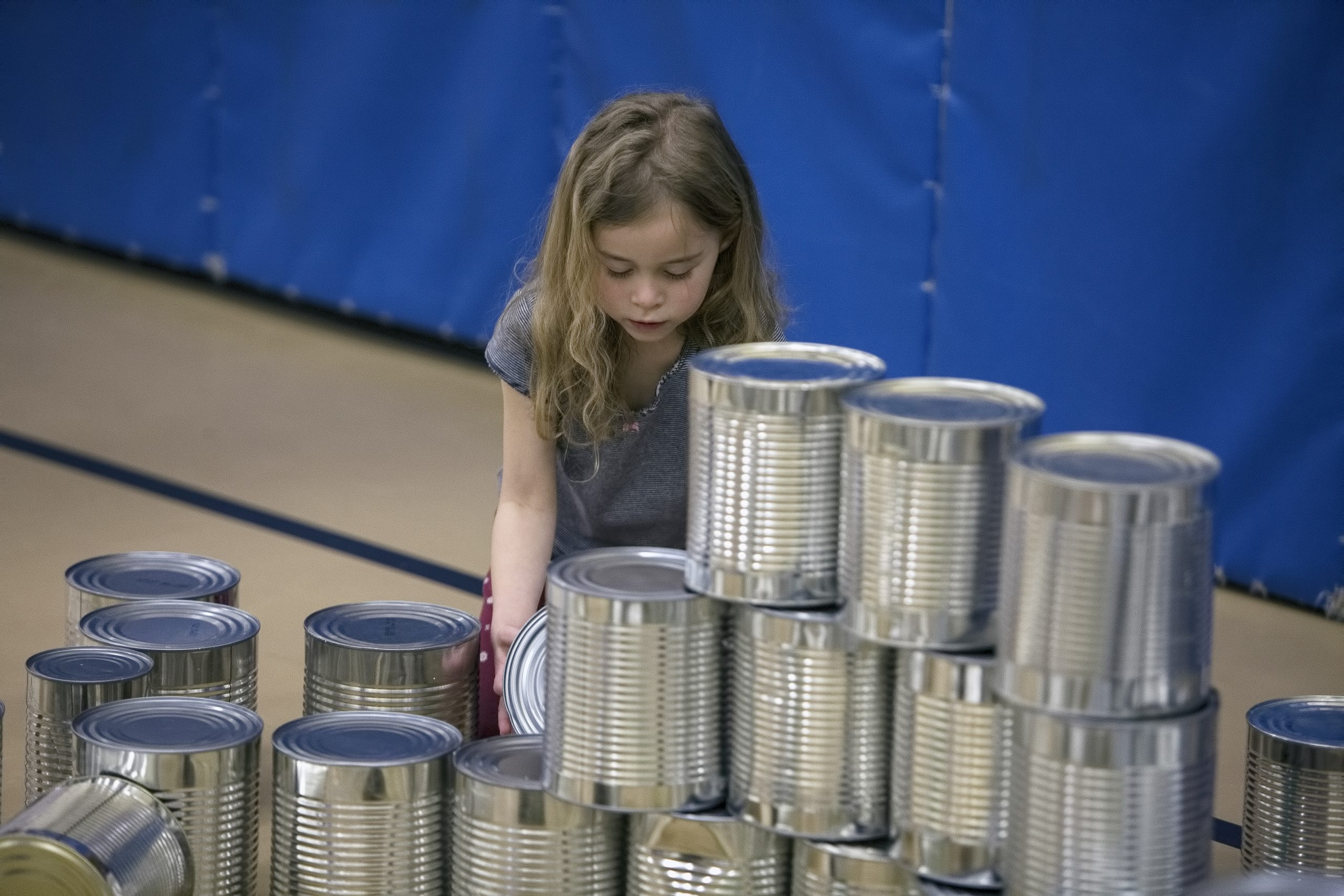 Female student stacking tin cups