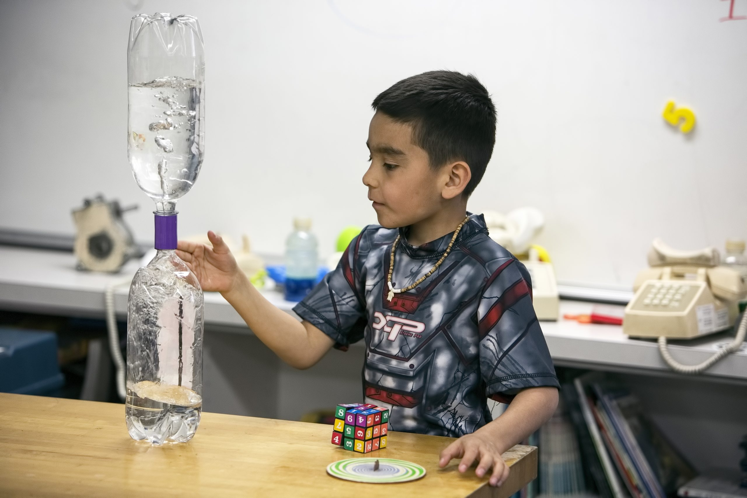 Male student experimenting with water bottle STEM project